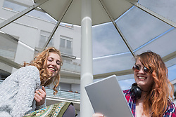 Young woman using a digital tablet with her friend, Munich, Bavaria, Germany