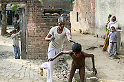 An elder villager is attacking Pardip, a 12-year-old boy from Simlana village, pop.4000, Saharanpur District, Uttar Pradesh, India, for no apparent reason, on Saturday, Mar. 29, 2008. Pardip developed a neurological disorder due to the long-term effects of consuming contaminated water at the age of two. Him and his family still use the 40 ft deep hand-pump located in their courtyard which provides water with large quantities of heavy metals and pesticides leaked through the ground from the nearby drains and the severely polluted Hindon river.