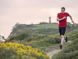 Man trail running on the cliff of Getxo