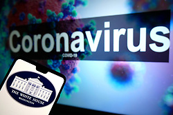 The White House logo seen displayed on a mobile phone with an illustrative model of the Coronavirus displayed on a monitor in the background. Photo credit should read: James Warwick/EMPICS Entertainment