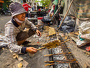 25 FEBRUARY 2015 - PHNOM PENH, CAMBODIA: A street food vendor grills catfish in front of the White Building. The White Building, the first modern apartment building in Phnom Penh, originally had 468 apartments, and was opened the early 1960s. The project was overseen by Vann Molyvann, the first Cambodian architect educated in France. The building was abandoned during the Khmer Rouge occupation. After the Khmer Rouge were expelled from Phnom Penh in 1979, artists and dancers moved into the White Building. Now about 2,500 people, mostly urban and working poor, live in the building. Ownership of the building is in dispute. No single entity owns the building, some units are owned by their occupants, others units are owned by companies who lease out apartments. Many of the original apartments have been subdivided since the building opened and serve as homes to two or three families. The building has not been renovated since the early 1970s and is in disrepair. Phnom Penh officials have tried to evict the tenants and demolish the building but residents refuse to move out.    PHOTO BY JACK KURTZ