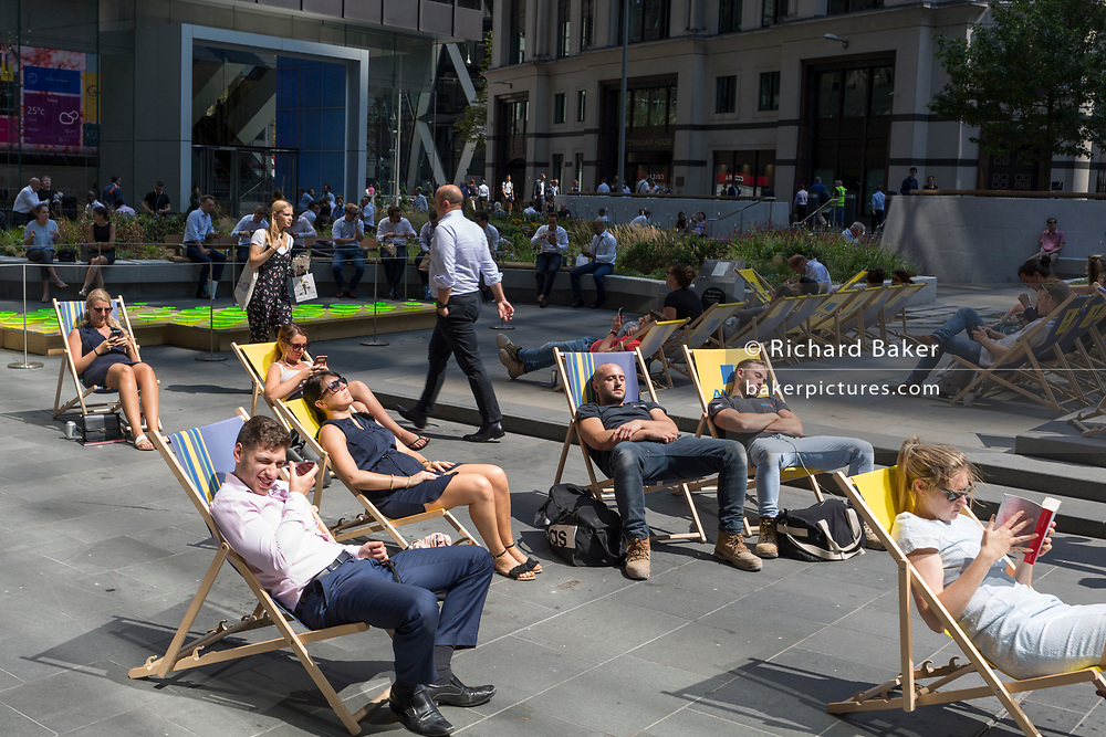 Office workers enjoy a lunchtime in Leadenhall during the 2018 heatwave in the City of London, the capital's financial district, on 24th July 2018, in London, England.