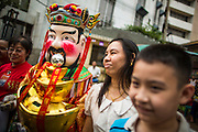 """10 FEBRUARY 2013 - BANGKOK, THAILAND:  A person dressed as a Chinese deity walks through the crowd soliciting donations for a temple during Chinese New Year celebrations on Yaowarat Road in Bangkok. Bangkok has a large Chinese emigrant population, most of whom settled in Thailand in the 18th and 19th centuries. Chinese, or Lunar, New Year is celebrated with fireworks and parades in Chinese communities throughout Thailand. The coming year will be the """"Year of the Snake"""" in the Chinese zodiac.   PHOTO BY JACK KURTZ"""