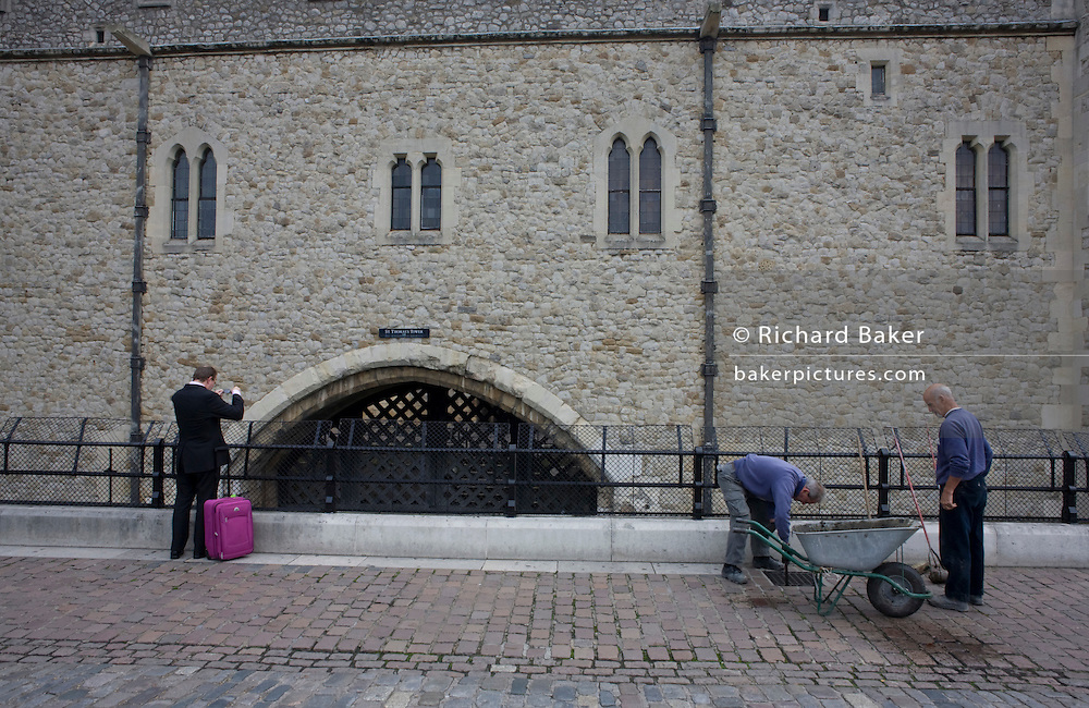 As workmen clean drains, a passing businessman pauses to photograph the notorious Traitors Gate at the Tower of London
