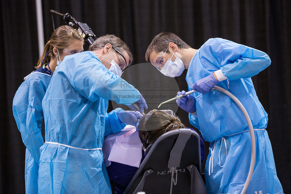 Volunteer dentists work on a tooth extraction during a free medical mission held by the SC Dental Association on August 23, 2013 in North Charleston, South Carolina. More than 1,000 people showed up to receive free dental and medical care.