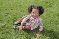 Young girl sitting on grass smiling,