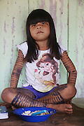 Surui girl whose body is painted with traditional blue/black tattoos<br /><br />An Amazonian tribal chief Almir Narayamogo, leader of 1350 Surui Indians in Rondônia, near Cacaol, Brazil, with a $100,000 bounty on his head, is fighting for the survival of his people and their forest, and using the world's modern hi-tech tools; computers, smartphones, Google Earth and digital forestry surveillance. So far their fight has been very effective, leading to a most promising and novel result. In 2013, Almir Narayamogo, led his people to be the first and unique indigenous tribe in the world to manage their own REDD+ carbon project and sell carbon credits to the industrial world. By marketing the CO2 capacity of 250 000 hectares of their virgin forest, the forty year old Surui, has ensured the preservation, as well as a future of his community. <br /><br />In 2009, the four clans and 25 Surui villages voted in favour of a total moratorium on logging and the carbon credits project. <br /><br />They still face deforestation problems, such as illegal logging, and gold mining which causes pollution of their river systems