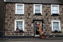 Jo Martin looks out of a window as a person in a dinosaur costume runs along the main street in Callander, Perthshire as the UK continues in lockdown to help curb the spread of the coronavirus.