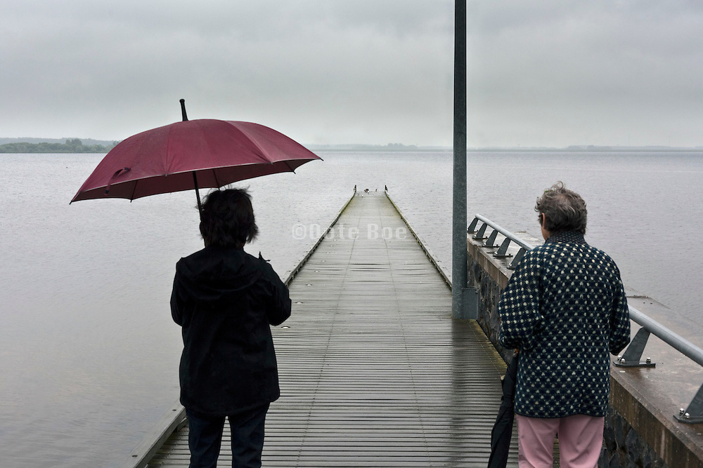 standing on a pier looking out over the water on a grey rainy day