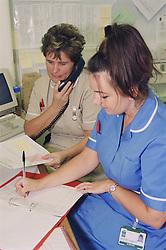 Senior staff nurse and nursing auxiliary at work at nurses station,