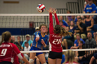 Gilford's Brooke Beaudet spikes the ball past Laconia's Taylor Morrill during NHIAA Division II Volleyball on Saturday evening.  (Karen Bobotas/for the Laconia Daily Sun)