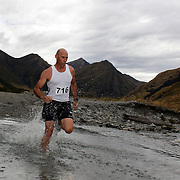 Runner Bruce McLean crosses  Moke Creek on the Ben Lomond High Country Station during the Pure South Shotover Moonlight Mountain Marathon and trail runs. Moke Lake, Queenstown, New Zealand. 4th February 2012. Photo Tim Clayton