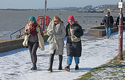 © Licensed to London News Pictures 13/02/2021.        Southend, UK. Friends walking along the seafront near Chalkwell Beach in freezing cold windy weather condition in Southend-on-Sea, Essex. Photo credit:Grant Falvey/LNP