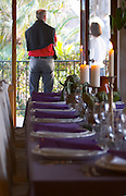 The dining room table decorated and set with flowers and decorative vegetables for dinner guests. A man and woman standing with his back to the camera on the balcony outside the dining room Clos des Iles Chambres d'Hotes Bed and Breakfast Le Brusc Six Fours Cote d'Azur Var France
