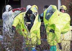 © Licensed to London News Pictures. 08/03/2018. Salisbury, UK. Firefighters are helped from their hazardous material suits after adjusting a police tent covering a park bench next to The Maltings shopping centre in Salisbury where Former Russian spy Sergei Skripaland his daughter Yulia were found after being poisoned with nerve agent. The couple where found unconscious on bench in Salisbury shopping centre. Authorities continue to investigate. Photo credit: Peter Macdiarmid/LNP