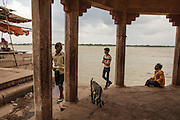 Men and a goat at Dattatreya Ghat, by the Ganges river, in Varanasi, India.
