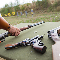 Competitor picks up his gun from a loading table during the Cowboy Action Shooting European Championship in Dabas, Hungary on August 11, 2012. ATTILA VOLGYI