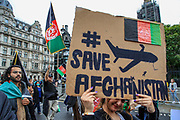 """Afghan women carry placards as they march towards Parliament Square during a protest """"Save Afghanistan"""" to protest the resurgence of the Taliban outside Downing Street, Britain's PM Office in central London on Saturday, Aug 21, 2021. (VX Photo/ Vudi Xhymshiti)"""