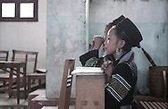 Young Hmong girls kneel and clasp their hands in prayer in a Sapa church, Vietnam, Lao Cai Province, Southeast Asia