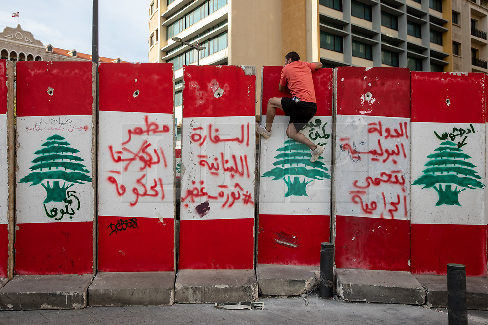 © Licensed to London News Pictures. 27/01/2020. Beirut, Lebanon. A man climbs onto a security barricade seen in front of the Grand Serail (Government Palace), in Downtown Beirut, as the government votes on the 2020 budget. Anti government demonstrators have been campaigning against government corruption and economic crisis for 103 days in Lebanon. Photo credit : Tom Nicholson/LNP