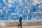 Man passes azulejos Portuguese blue and white wall tiles of Capela das Almas de Santa Catarina  - St Catherine's Chapel in Porto, Portugal