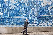 Man passes azulejos Portuguese blue and white wall tiles of Capela das Almas de Santa Catarina  - St Catherine's Chapel in Porto, Portugal