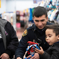 """Lori Gallindo from Grants Head Start and Erik Gallindo, a police officer with Grants Police Department help Said Mendoza, 4, a student at Grants Head Start shop for clothes at Walmart, Wednesday Dec. 19 during their annual """"Shop with a Cop"""" event."""