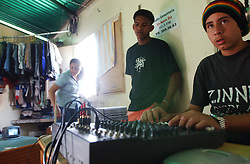 """Davis Semeco, right, plays music during his radio show on """"A New Day Radio"""", a community radio station in Caracas.  The station operates out of a home in a Caracas slum. Chavez and his government have been increasingly supportive of these generally Chavista community media stations as a response to the anti-chavista private media."""