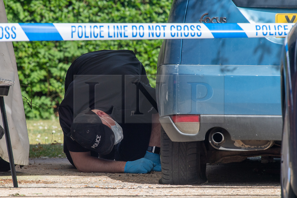 © Licensed to London News Pictures. 21/05/2020. Beaconsfield, UK. A specialist search team member searches under a blue car at a property on North Drive. Thames Valley Police were called to North Drive, Beaconsfield at around 00:01 BST on Thursday 21/05/2020 to a report of a stabbing. A man in his forties had sustained injuries consistent with stab wounds and was taken to hospital. Photo credit: Peter Manning/LNP
