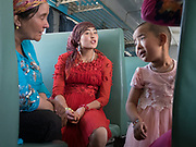Aïgul and her mother chats with the neighbors. Life inside the train - mostly Muslim Uighur people  ride this train.