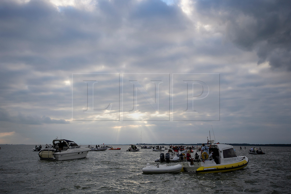 © Licensed to London News Pictures. 18/09/2016. Portsmouth, UK. The boats arrive at the bank. Teams take part in the  Bramble Bank Cricket Match in the middle of The Solent strait on September 18, 2016. The annual cricket match between the Royal Southern Yacht Club and The Island Sailing Club, takes place on a sandbank which appears for 30 minutes at lowest tide. The game lasts until the tide returns. Photo credit: Ben Cawthra/LNP