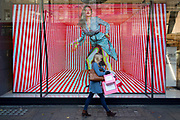 A pre-Christmas shopper walks past a video ad loop for the London retailer 'Reserved', on Oxford Street, on 23rd November 2017, in London England.