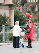 Local woman talking to man dressed as a Roman centurion, Rome, Italy
