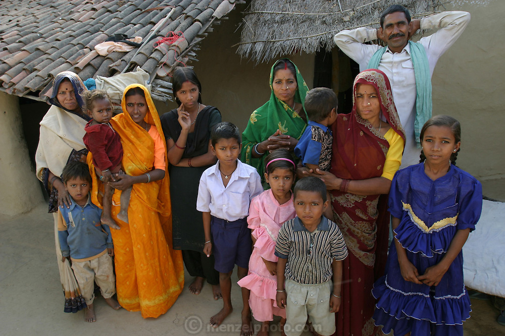 Yadav family portrait, including their extended family from the neighboring village where Mishri Yadav (in maroon) was born, in the courtyard of their home during a revisit with the family, 2004. Ahraura Village, Uttar Pradesh, India. The Yadavs were India's participants in Material World: A Global Family Portrait, 1994 (pages: 64-65), for which they took all of their possessions out of their house for a family-and-possessions-portrait. Child, Children. Work..