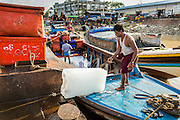 17 JUNE 2013 - YANGON, MYANMAR:  Men load ice blocks onto a fishing boat in a large Yangon fish market. The market serves both domestic retail customers and wholesale international customers. With thousands of miles of riverine waterways and ocean coastline Myanmar has a large seafood and fishing industry.     PHOTO BY JACK KURTZ