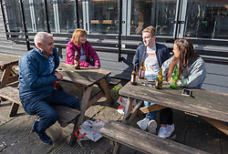 © Licensed to London News Pictures; 21/03/2020; Bristol, UK. Coronavirus Pandemic; a family with their own drinks enjoy the sunshine in the open air in King Street which is normally full of people at the weekend with all the pubs open, the day after the UK's prime minister ordered the closure of all pubs, bars, cafes, restaurants and gyms to try and prevent the spread of the coronavirus. The UK Government is urging people to self isolate but also to get fresh air and exercise outside with social distance between people. Photo credit: Simon Chapman/LNP.