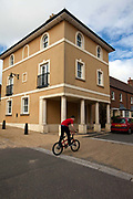 A boy rides his bicycle past a traditionally styled building in Poundbury. Poundbury on Duchy of Cornwall land is Prince Charles' attempt to create an urban extension to Dorchester famed for Its pastiche of traditional architecture. Dorset, UK