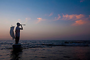 Silhouette of a man standing in a bathtub like boat with a telescope