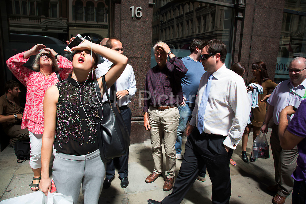 """London, UK. Thursday 5th September 2013. City workers looking up into the light. Urgent action in planned to """"cover up"""" the Walkie Talkie skyscraper in the City after sunlight reflected from the building melted a car on the streets below. Temperatures have been measured in excess of 50 degrees C, and as much as 70 degrees at it's peak. The 525ft building has been renamed the """"Walkie Scorchie"""" after its distinctive concave surfaces reflected a dazzling beam of light which has caused extensive damage to nearby buildings."""