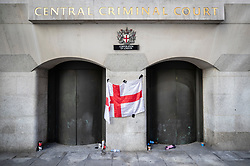 © Licensed to London News Pictures . 27/09/2018. London, UK. A flag of St George remains stuck to the front of The Old Bailey after former EDL leader Tommy Robinson's retrial for Contempt of Court was adjourned - following his actions outside Leeds Crown Court in May 2018 . Robinson was already serving a suspended sentence for the same offence when convicted in May and served time in jail as a consequence , but the newer conviction was quashed by the Court of Appeal and a retrial ordered . Photo credit: Peter Macdiarmid/LNP