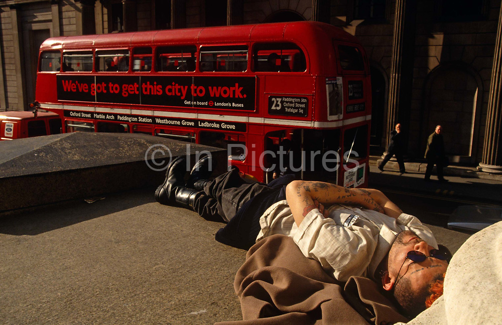 man is lying down on the steps of Royal Exchange opposite the Bank of England in the City of London, to take a nap under a mid-day sun in the heart of the capital's financial district. A red double-decker Routemaster bus has stopped in a queue of traffic opposite with an advert for London buses saying 'We've got to get this city to work' but with tattoos on his arms and his forehead and wearing heavy army-style boots, he is clearly not on his way to a job and therefore out-of-place in this busy part of London. With arms folded and head resting on an unseasonal coat, the man is asleep and going nowhere.