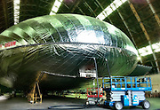 Thunderbird 2 flies again: The astonishing airship set to revolutionise haulage, tourism... and warfare<br /> <br /> A radical new kind of airship funded by the US military is about to make its first test flight - and it looks uncannily like the Thunderbird 2 craft from the classic TV show.<br /> The Aeroscraft airship will carry three times as much as the biggest military cargo planes over thousands of miles, use a third of the fuel, and it doesn't even need a landing strip.<br /> It could also have major implications for cargo haulage, and almost everything now laboriously transported across the planet's surface by boat, train and lorry could within years be carried through the skies, its makers claim.<br /> California-based aviation firm Aeros, with heavy backing from the U.S. military, has been developing their revolutionary Aeroscraft for several years, and they say the airship is now in its final stages.<br /> They have built a prototype which they hope will finally prove the concept works in practice and allow them to fine tune their systems.<br /> At 77m (250ft) in length, it is just half the size of the final model, but has been built with the same rigid structure, flight control systems and landing gear.<br /> Now all that needs to be done is for it to demonstrate the vertical take-off and landing that will make possible the point-to-point delivery features that will make it perfect for the commercial market.<br /> <br /> The finished version of the Aeroscraft - expected to be ready in three years - will carry a payload of 66 tons at a speed of 120 knots, upto 18,000ft with a range of 3000 nautical miles.<br /> That could revolutionise air transport, opening up remote areas where there is practically no other means of access.<br /> It could carry relief supplies for victims in disaster areas, heavy oil-extraction equipment to northern Canada's tar sands, huge turbines to remote wind farms and, of course, heavy military equipment to battlefields worldwide.<br /> <br /> The key breakthrough has been the development of an internal system for