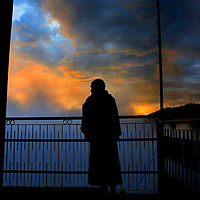 A buddhist monk pauses on the way to prayer to take in a fiery sunset from a porch at the Dalai Lama Temple in Dharamsala, India.<br /> Photo by Shmuel Thaler <br /> shmuel_thaler@yahoo.com www.shmuelthaler.com