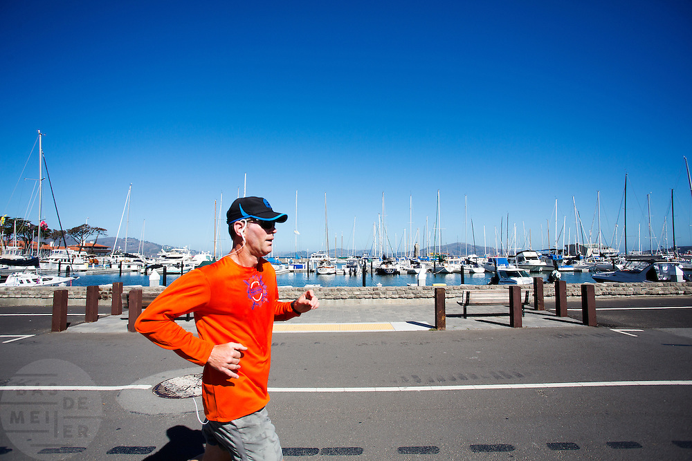 Een man rent langs een haven in San Francisco. De Amerikaanse stad San Francisco aan de westkust is een van de grootste steden in Amerika en kenmerkt zich door de steile heuvels in de stad.<br /> <br /> A man runs at the harbour in San Francisco. The US city of San Francisco on the west coast is one of the largest cities in America and is characterized by the steep hills in the city.