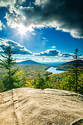 The sun breaks through the clouds, illuminating the early autumn forest surrounding Kettle Pond in this view from the summit of Owl's Head Mountain in the Groton State Forest, Vermont. Owl's Head Mountain has an elevation of 1958 feet (597 meters). Hardwood Mountain, with an elevation of 2,172 feet (662 meters) is visible to the left of Kettle Pond. The White Mountains of New Hampshire are visible at the horizon in the background.