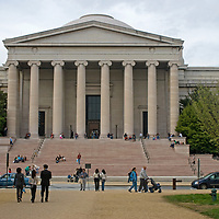 Tourists sit and wander in front of the West Building of the National Museum of Art in Washington, DC.
