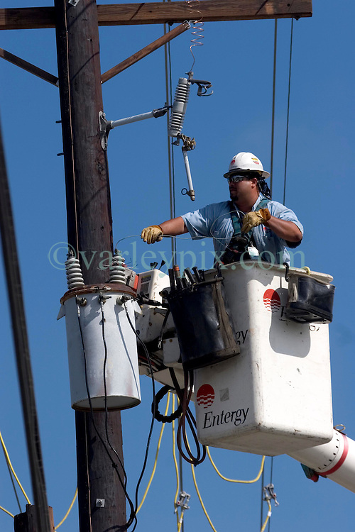 03 Oct, 2005.  New Orleans, Louisiana. Hurricane Katrina aftermath.<br /> Linemen from the electricity company Entergy restring power lines to the 9th ward in New Orleans.<br /> Photo; ©Charlie Varley/varleypix.com