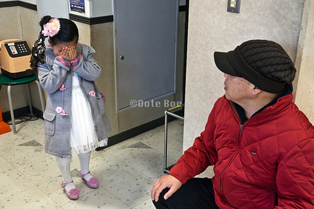 little girl holding her hand in front of her face with adult person looking on