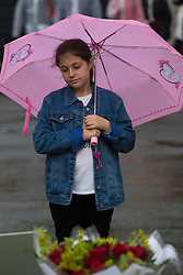 Parliament Square, Westminster, London, June 17th 2016. Following the murder of Jo Cox MP friends and members of the public lay flowers, light candles and leave notes of condolence and love in Parliament Square, opposite the House of Commons. PICTURED: A girl looks at the hundreds of bouquets and written tributes as the rain falls in Parliament Square.