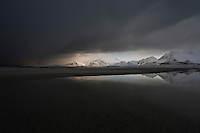 Dark clouds of approaching winter storm cover mountain landscape from Ytresand beach, Moskenesøy, Lofoten Islands, Norway
